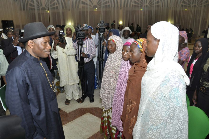 Nigerian President Goodluck Jonathan greets some schoolgirls who escaped abduction from the Chibok government secondary school in Abuja, Nigeria. Mr. Jonathan, who faces re-election in 2015, disclosed that he has authorized third parties to try to secure the rest of the girls' safe release from the extremist group Boko Haram. (Associated Press)