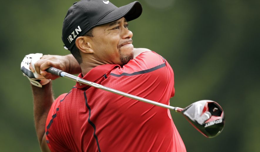 Tiger Woods watches his his tee shot on the fourth hole during the final round of the Bridgestone Invitational golf tournament Sunday, Aug. 3, 2014, at Firestone Country Club in Akron, Ohio. (AP Photo/Mark Duncan)