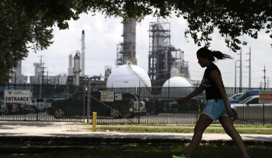 A teenage girl walks around the track of a park across the street from the Valero refinery Monday, Aug. 4, 2014, in the Manchester neighborhood of Houston. An Environmental Protection Agency rule to require refineries to monitor emissions of benzene is to be publicly debated Tuesday near Houston. (AP Photo/Pat Sullivan)