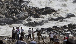 ** FILE ** People stand at the banks of the River Sunkoshi near the site of a massive landslide in Mankha village, about 120 kilometers (75 miles) east of Katmandu, Nepal, Monday, Aug. 4, 2014. (AP Photo/Niranjan Shrestha)