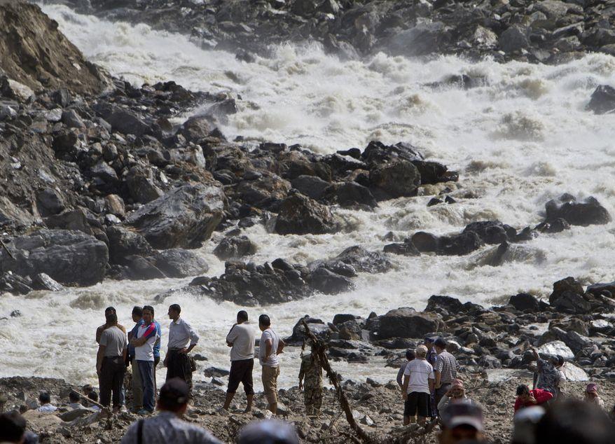 ** FILE ** People stand at the banks of the River Sunkoshi near the site of a massive landslide in Mankha village, about 120 kilometers (75 miles) east of Katmandu, Nepal, Monday, Aug. 4, 2014. (AP Photo/Niranjan Shrestha)