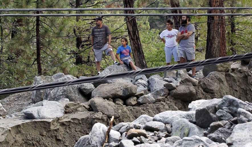 Onlookers view rocks and mud and downed power lines from a mudslide in the mountain community of Forest Falls in the San Bernardino Mountains Monday, Aug. 4, 2014. Crews cleared roads in an area where some 2,500 had been stranded after thunderstorms caused mountain mudslides in Southern California over the weekend, while authorities estimated that between six and eight homes were badly damaged and likely uninhabitable. One person was found dead in a vehicle that was caught in a flash flood. A group of campers spent the night at a community center near Forest Falls. (AP Photo/Nick Ut)