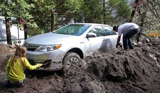 ** FILE ** Andrew Watson and Taylor Becker dig out their car after rocks and mud inundated their home in the mountain community of Forest Falls in the San Bernardino Mountains Monday, Aug. 4, 2014. Crews cleared roads in an area where some 2,500 had been stranded after thunderstorms caused mountain mudslides in Southern California over the weekend, while authorities estimated that between 6 and 8 homes were badly damaged and likely uninhabitable. (AP Photo/Nick Ut)