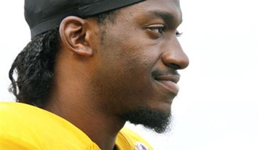 Robert Griffin III talks to the media after the Redskins and Patriots practice at the Redskins Training Camp in Richmond, Va., Monday, August 4, 2014.  (AP Photo/Richmond Times-Dispatch, Alexa Welch Edlund)