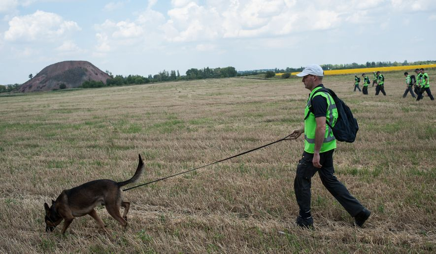 Australian, Malaysian and Dutch investigators continue to examine the area of the downed Malaysia Airlines Flight 17, near the village of Rossipne, Donetsk region, eastern Ukraine, Tuesday, Aug. 5, 2014. The West has accused Russia of most likely providing the insurgents with surface-to-air missiles that may have been used to shoot down the Malaysia Airlines passenger jet over rebel-held territory on July 17, killing all 298 people on board. (AP Photo)