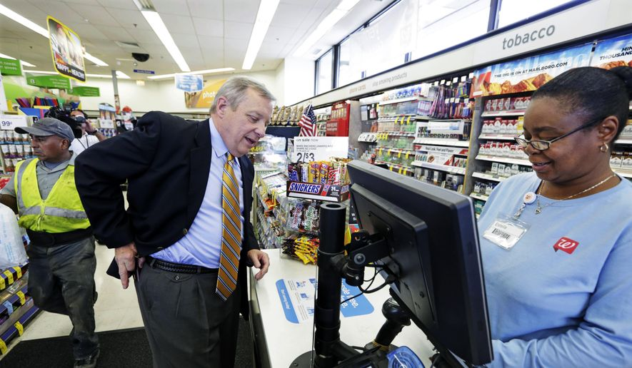 U.S. Sen. Dick Durbin, D-Ill., talks to Walgreens clerk Estella Washington as he shops after a news conference Wednesday, Aug. 6, 2014, in Chicago. Durbin praised Walgreen, the nation's largest drugstore chain, for declining to pursue an overseas reorganization to trim its U.S. taxes. (AP Photo/M. Spencer Green) **FILE**