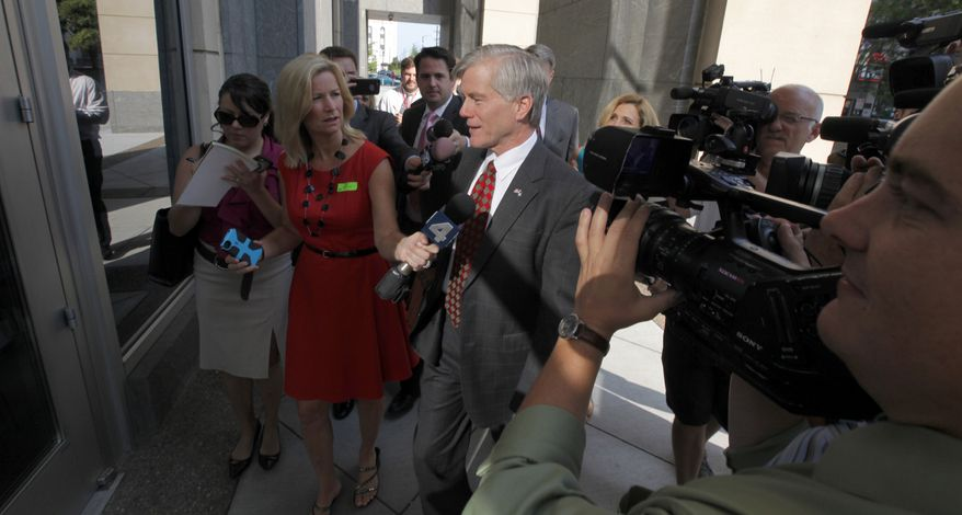 Former Virginia Gov.Bob McDonnell, center, heads into the federal courthouse in Richmond, Va., Wednesday, Aug. 6, 2014, as the federal corruption trial against him and former first lady Maureen McDonnell continues. The McDonnells are charged with accepting more than $165,000 in gifts and loans from Jonnie Williams, the former CEO of dietary supplements maker Star Scientific Inc., in exchange for helping promote his company's products. (AP Photo/Richmond Times-Dispatch, Bob Brown)