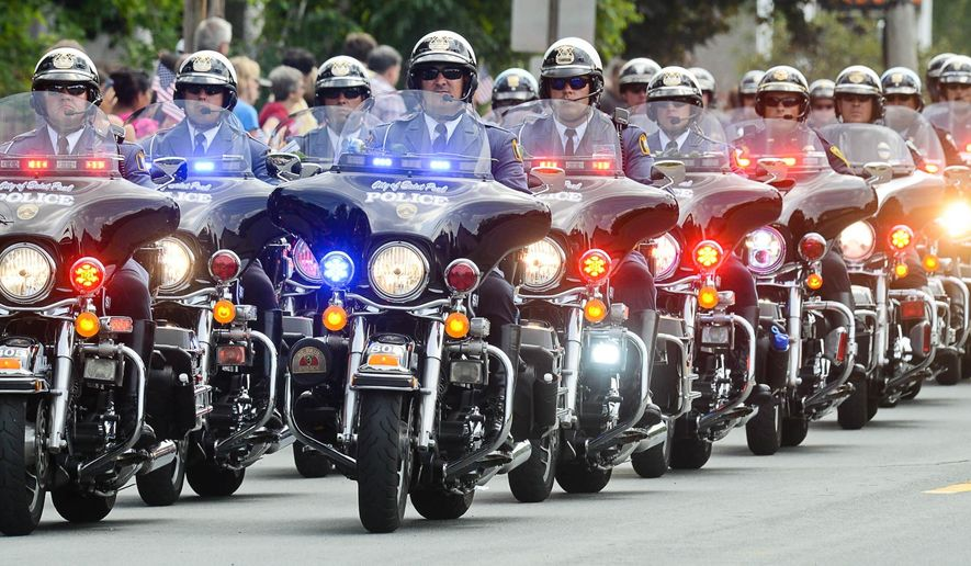 A group of St. Paul police officers on motorcycles lead the funeral procession for Mendota Heights police officer Scott Patrick from St. Stephen's Lutheran Church in West St. Paul, Minn. on Wednesday, Aug. 6, 2014. Patrick, 47, was shot and killed while making a traffic stop on Wednesday, July 30, 2014. (AP Photo/St. Paul Pioneer Press, Ben Garvin)