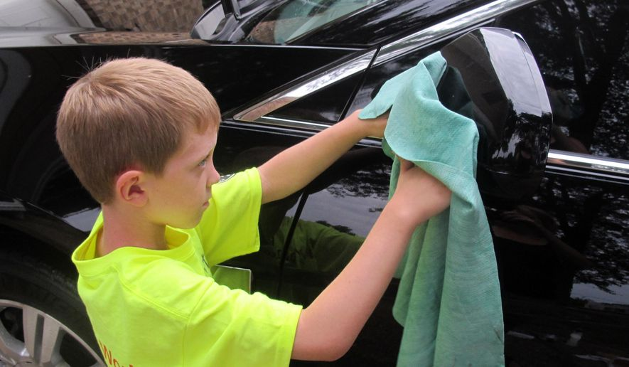 In this July 18, 2014 photo, Sterling Murset washes a car at the home of Todd Blanchieri in Pensacola, Fla. The Murset family is touring the country doing chores for families in need. (AP Photo/Melissa Nelson-Gabriel)