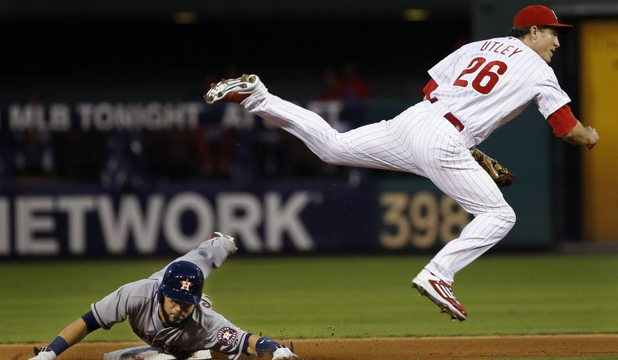 Philadelphia Phillies second baseman Chase Utley leaps over Houston Astros' Marwin Gonzalez after forcing him out at second on a ball hit by Jake Marisnick during the fourth inning of an interleague baseball game, Thursday, Aug. 7, 2014, in Philadelphia. Marisnick was safe at first on the play. (AP Photo/Matt Slocum)