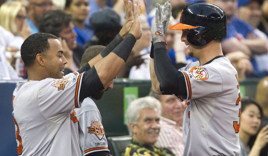 Baltimore Orioles' Caleb Joseph, right,  is congratulated by teammate Nelson Cruz after he hit a two run home run off Toronto Blue Jays starting pitcher J.A. Happ during fourth inning baseball action in Toronto Thursday,  Aug. 7, 2014. (AP Photo/The Canadian Press, Fred Thornhill)