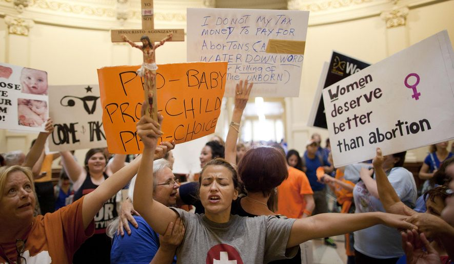 In this July 12, 2013, file photo, anti-abortion rights supporter Katherine Aguilar holds a crucifix and prays while opponents and supporters of abortion rights gather in the State Capitol rotunda in Austin, Texas. Nearly three-quarters of Texas' 18 abortion facilities would be forced to close by the end of Aug. 2014 if one of the nation's toughest new anti-abortion laws is allowed to take effect, attorneys for clinics challenging the law told a federal judge Monday, Aug. 4, 2014. (AP Photo/Tamir Kalifa, File)