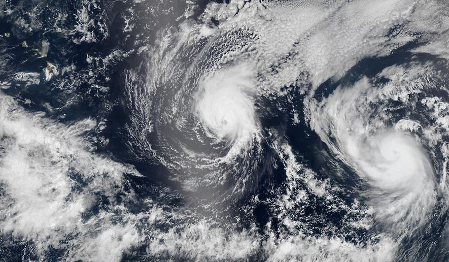 This Aug. 5, 2014 satellite image provided by NASA shows two tropical Pacific Ocean hurricanes - Iselle at center and Julio at right - bearing down on Hawaii, top left. Hurricane Iselle is expected to reach Hawaii Thursday night, Aug. 7, 2014. Tracking close behind it is Hurricane Julio, which strengthened early Thursday into a Category 2 storm. (AP Photo/NASA)