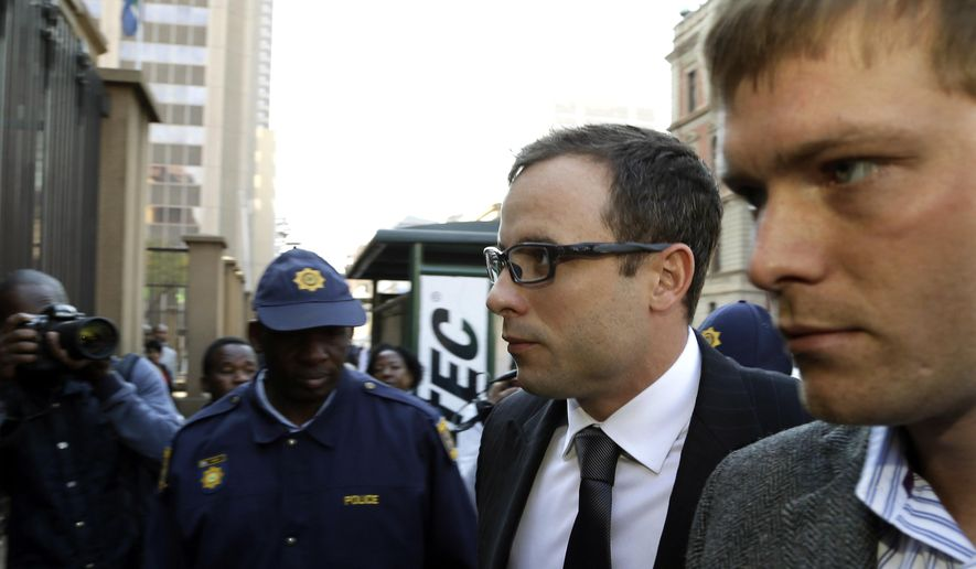 Oscar Pistorius, second from right, accompanied by a relative arrives at the high court in Pretoria, South Africa, Thursday, Aug. 7, 2014. On Thursday and Friday, both sides will summarize their versions of the shooting to Thokozile Masipa, the red-robed judge who will determine the fate of the double-amputee Olympic runner. (AP Photo/Themba Hadebe)