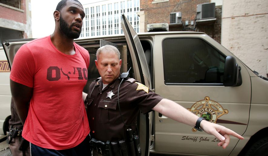 Greg Oden is escorted into the Marion County Community Corrections building, Thursday, Aug. 7, 2014, in Indianapolis. Police arrested former NBA No. 1 draft pick Greg Oden on battery charges early Thursday, alleging that he punched his ex-girlfriend in the face during a fight at his mother's suburban Indianapolis home. (AP Photo/The Indianapolis Star, Brent Drinkut)  NO SALES
