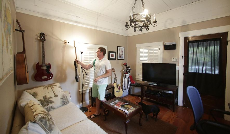 "In this July 30, 2014 photo, Renter Matthew Clarie hangs a guitar in the living room of his 388-square-foot home in Hyde Park, Fla. Tom Scarritt, 57, a lawyer, bought the home with his wife, Linda, a decade ago, convinced it would make a good one-room rental for ""singles and short people."" He would call it a ""shotgun shack,"" but you can't fire from one door clean through the back. The house has only one door. (AP Photo/The Tampa Bay Times, James Borchuck)  TAMPA OUT; CITRUS COUNTY OUT; PORT CHARLOTTE OUT; BROOKSVILLE HERNANDO TODAY OUT"