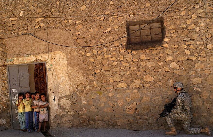 Children look on as Sgt. David Ristau, 172nd Stryker Brigade Combat Team, provides security during a patrol in Sinjar's market district in 2006. (U.S. Air Force via Associated Press)