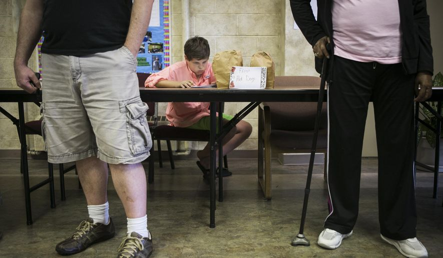 George Sentilles, 12, looks at a math problem as he does his homework while his mom, Katie Sentilles, exercises her right to vote at Trinity United Methodist Church Educational Center in Memphis, Tenn. Thursday, Aug. 7, 2014. (AP Photo/The Commercial Appeal, Yalonda M. James)