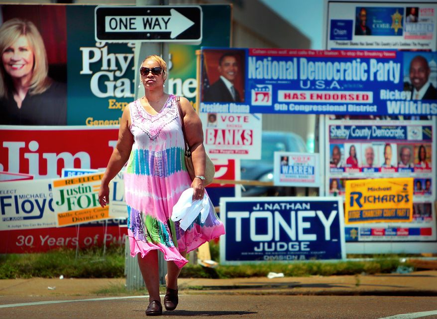 Annette Mallet passes a wall of campaign signs on Poplar Ave. Wednesday, Aug. 6, 2014  near the Shelby County Election Commission Offices in Memphis, Tenn. More than two dozen incumbent Republican and Democratic state lawmakers face challengers in Thursday's primary elections, and several could swing on narrow margins.  (AP Photo/The Commercial Appeal, Jim Weber)