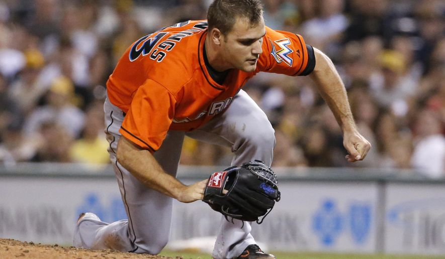 Miami Marlins relief pitcher Dan Jennings falls to the ground after being hit by a line drive off the bat of Pittsburgh Pirates' Jordy Mercer during the seventh inning of a baseball game in Pittsburgh Thursday, Aug. 7, 2014. Jennings was driven off the field. (AP Photo/Gene J. Puskar)