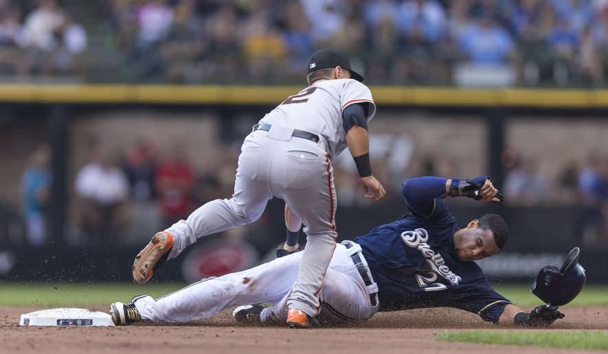 Milwaukee Brewers' Carlos Gomez is tagged out by San Francisco Giants' Joe Panik on a steal attempt during the first inning of a baseball game Thursday, Aug. 7, 2014, in Milwaukee. (AP Photo/Tom Lynn)