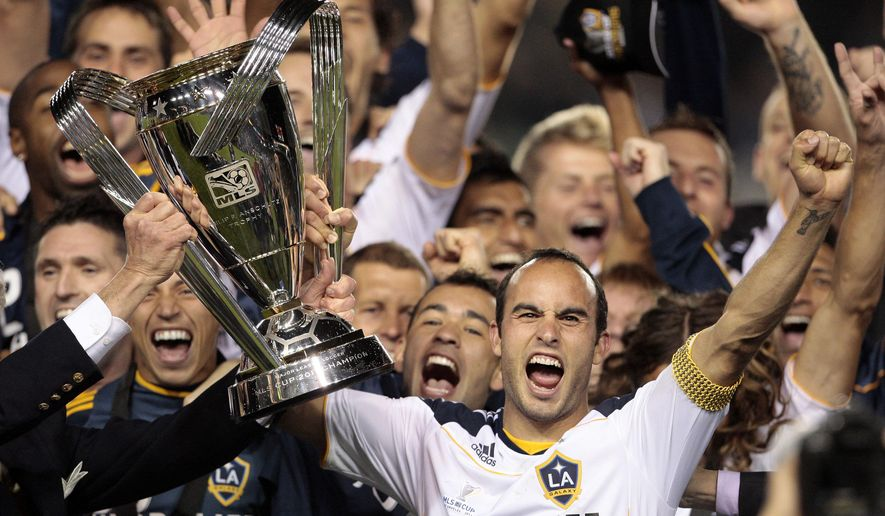 FILE - In this Nov. 20, 2011 file photo, Los Angeles Galaxy forward Landon Donovan holds up the MLS Cup after they won their championship soccer match against the Houston Dynamo in Carson, Calif. Landon Donovan says he will retire from professional soccer at the end of the MLS season. The LA Galaxy forward is widely considered the best soccer player in American history.  (AP Photo/Bret Hartman)
