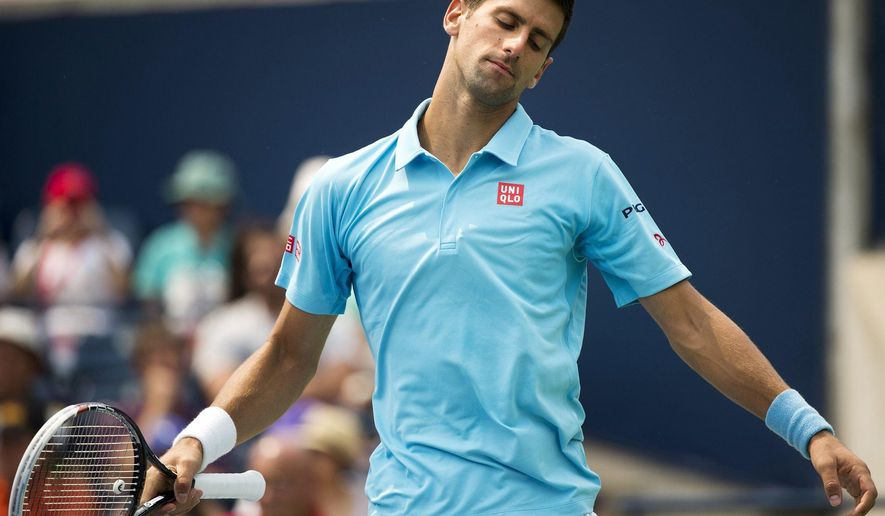 Novak Djokovic, of Serbia, reacts while playing against Jo-Wilfried Tsonga, of France, in a men's third round match at the Rogers Cup tennis tournament action in Toronto Thursday, Aug. 7, 2014. (AP Photo/The Canadian Press, Nathan Denette)