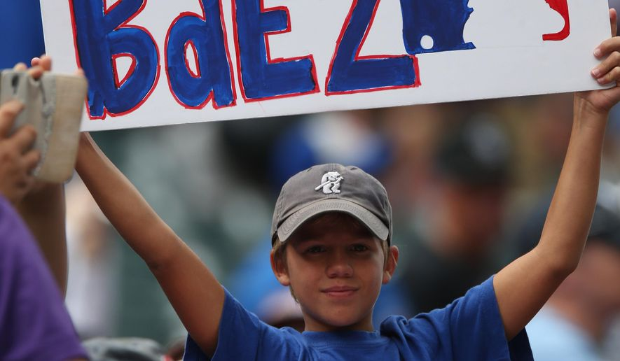 A young fan of the Chicago Cubs holds up placard to welcome the Cubs second baseman Javier Baez who was about to play in his third game since being called up from the Cubs farm team in Iowa as the Cubs face the Colorado Rockies in  a baseball game in Denver on Thursday, Aug. 7, 2014. (AP Photo/David Zalubowski)