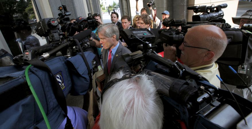 Former Virginia Gov. Bob McDonnell is surrounded by members of the media as he heads into the federal courthouse in Richmond, Va., Thursday, Aug. 7, 2014, where the federal corruption trial of McDonnell and his wife, Maureen continues. The McDonnells are charged with accepting more than $165,000 in gifts and loans from Jonnie Williams, the former CEO of dietary supplements maker Star Scientific Inc., in exchange for helping promote his company's products.  (AP Photo/Richmond Times-Dispatch, Bob Brown)