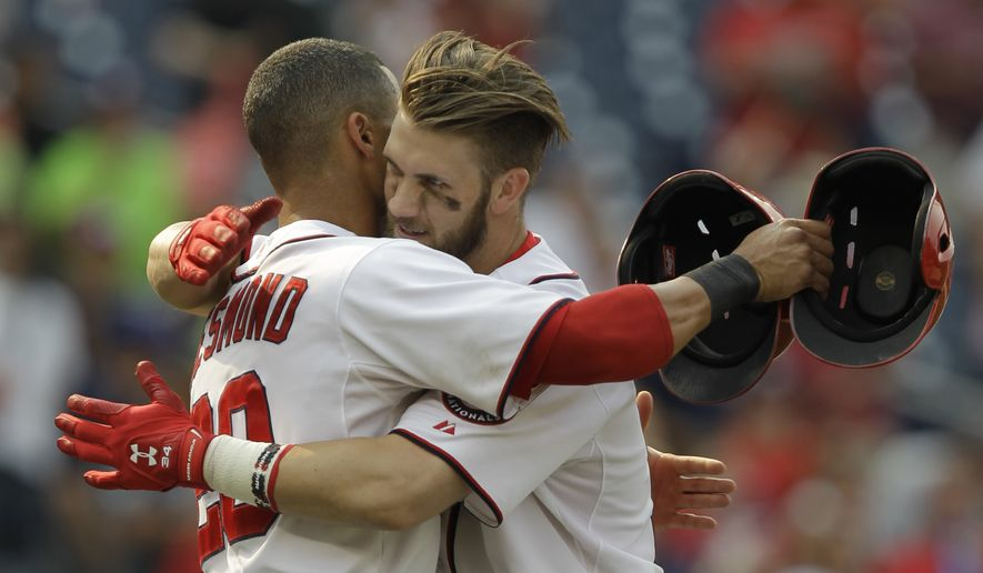Washington Nationals' Ian Desmond, left, hugs teammate Bryce Harper, right, after Harper hit a  two-run home run during the thirteenth inning of a baseball game against the New York Mets, Thursday, Aug. 7, 2014, in Washington. The Nationals won 5-3 in thirteen innings. (AP Photo/Luis M. Alvarez)