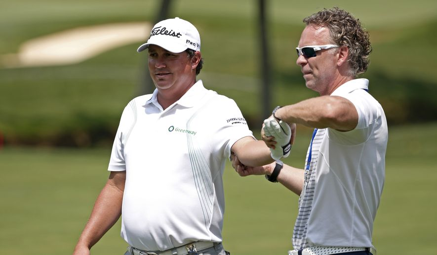 Jason Dufner, left, get treatment on the 16th hole during a practice round for the PGA Championship golf tournament at Valhalla Golf Club on Wednesday, Aug. 6, 2014, in Louisville, Ky. The tournament is set to begin on Thursday. (AP Photo/Mike Groll)