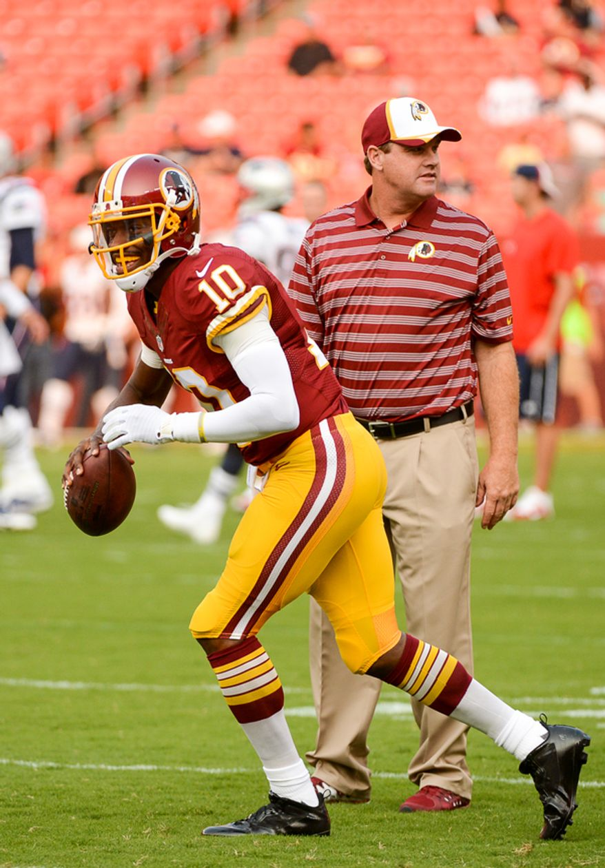 Washington Redskins quarterback Robert Griffin III (10) and Washington Redskins head coach Jay Gruden on the field together during warm ups before the Washington Redskins play the New England Patriots in NFL preseason football at FedExField, Landover, Md.,  Thursday, August 7, 2014. (Andrew Harnik/The Washington Times)Monday, September 9, 2013. (Andrew Harnik/The Washington Times)