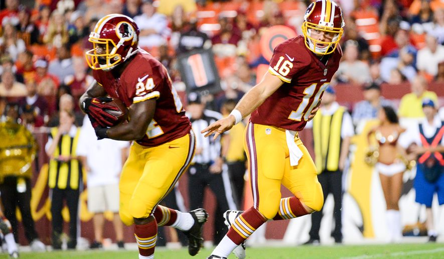 Washington Redskins quarterback Colt McCoy (16) hands off to Washington Redskins running back Silas Redd as the Washington Redskins play the New England Patriots in NFL preseason football at FedExField, Landover, Md.,  Thursday, August 7, 2014. (Andrew Harnik/The Washington Times)