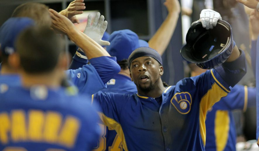 Milwaukee Brewers' Rickie Weeks, is congratulated by team mates after hitting a three run home run against the Los Angeles Dodgers during the eighth inning of a baseball game Friday, Aug. 8, 2014, in Milwaukee. (AP Photo/Darren Hauck)