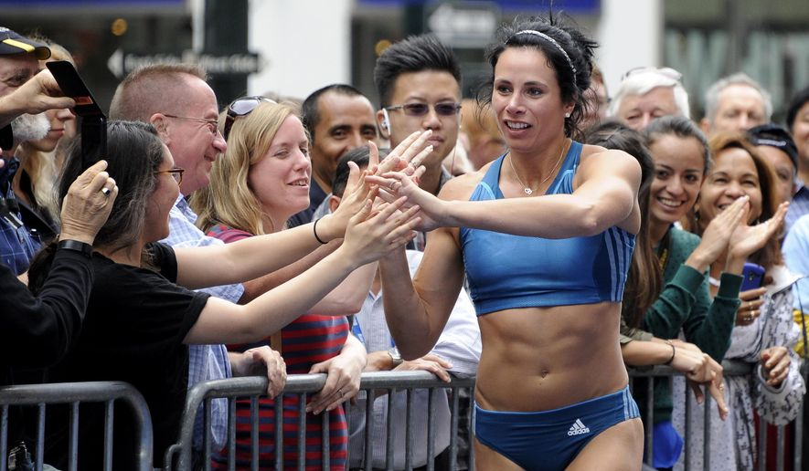 FILE - In this Jule 11, 2014 file photo, Olympic pole vault champion Jenn Suhr celebrates with fans after clearing 15 feet, 6 inches to win the Adidas Grand Prix pole vault event in Herald Square in New York.  Suhr has injured her hand, torso and neck after her pole snapped during a practice session at her western New York training facility. The 32-year-old Suhr was working out Wednesday, Aug. 6, 2014, at her home in Riga, outside Rochester, when her pole shattered halfway into her ascent while attempting to clear 15 feet. (AP Photo/Kathy Kmonicek, File)