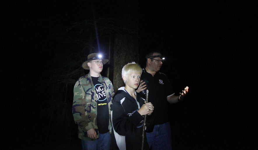 In this July 11, 2014 photo, John Ray, of Marysville, right, and his sons, Mike, 16, left, and Christopher, 12, investigate the forest for signs of bigfoot activity off the Mountain Loop Highway outside of Granite Falls, Wash. Ray and fellow investigator Rob Parker, of Snohomish, work for the Bigfoot Field Researchers Organization checking out areas where bigfoot activity has been reported. (AP Photo/The Herald, Genna Martin)