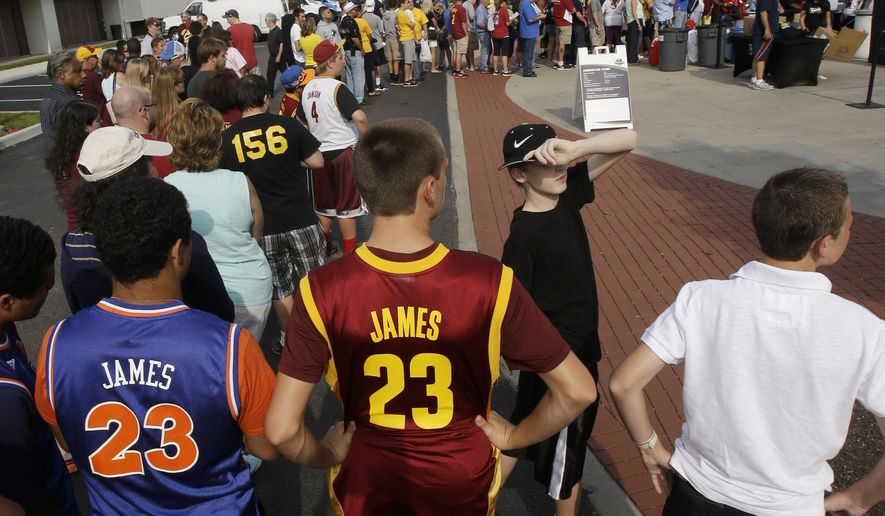 From left to right, Bryce Traylor and Corey Oswald, both 14, wait in line to enter InfoCision Stadium for the LeBron James homecoming Friday, Aug. 8, 2014, in Akron, Ohio. James is being welcomed back Friday night by the city where he first bounced a basketball. James grew up in Akron and has maintained a strong connection with his hometown. (AP Photo/Tony Dejak)
