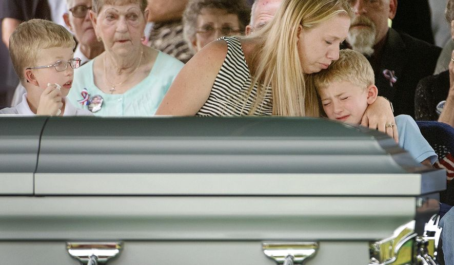 "Liz Prange, the widow of U. S. Army Staff Sgt. Benjamin G. Prange, consoles her 8-year-old son, Dillon, right, as her son Corbin, 10, looks on during the playing of ""Amazing Grace"" on Friday, Aug. 8, 2014, during the soldier's burial at Lincoln Memorial Park, in Lincoln, Neb. Prange died in Afghanistan on July 24, after the vehicle he was riding in hit an explosive device. (AP Photo/Lincoln Journal Star, Francis Gardler)"