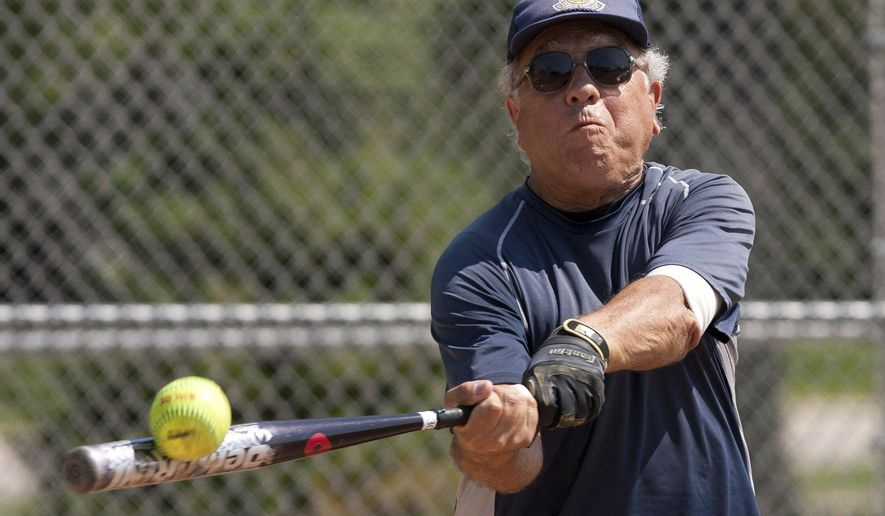 In this July 9, 2014 photo, Chris Argianas, 80, of Woodridge, Ill., drives a single to the outfield during a Naperville Men's Senior Softball League game at Gartner Park in Naperville, Ill. The league, sponsored by Naperville Park District, features about 40 guys -- many retired -- who range in age from their late 50s to their 70s. (AP Photo/Daily Herald, Daniel White)  MANDATORY CREDIT, MAGS OUT