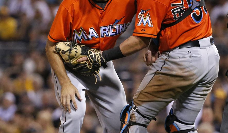 Miami Marlins relief pitcher Dan Jennings, left, is helped by catcher Jarrod Saltalamacchia as he begins to stagger after being hit by a line drive off the bat of Pittsburgh Pirates' Jordy Mercer during the seventh inning of a baseball game in Pittsburgh Thursday, Aug. 7, 2014.  (AP Photo/Gene J. Puskar)