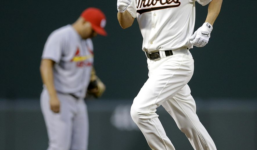 Baltimore Orioles' J.J. Hardy rounds the bases past St. Louis Cardinals shortstop Jhonny Peralta after hitting a solo home run in the third inning of an interleague baseball game, Friday, Aug. 8, 2014, in Baltimore. (AP Photo/Patrick Semansky)