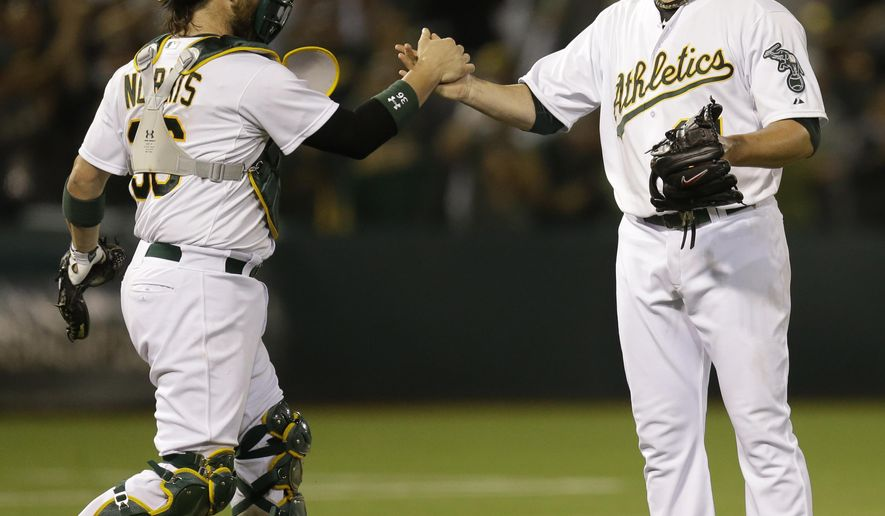 Oakland Athletics' Jon Lester, right, celebrates with catcher Derek Norris after the  A's 3-0 win over the Minnesota Twins in a baseball game Thursday, Aug. 7, 2014, in Oakland, Calif. (AP Photo/Ben Margot)