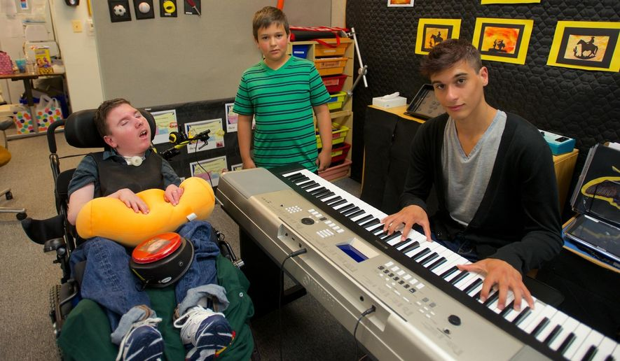 MEMBER EXCHANGE ADVANCE FOR SUNDAY, AUG. 10 - In this July 31, 2014 photo, 16-year-old Doug Anderson, right, poses with his twin brother Robbie, left, and younger brother Colton, rear, at Robbie's classroom at CREST school in Methuen, Mass., where Doug performed music for the special education students. (AP Photo/The Eagle-Tribune, Ryan Hutton)