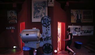 In this July 27, 2014 file photo, a moviegoer walks past an old projector on display at the entrance of the Zefyros vintage-movie cinema in Ano Petralona, near central Athens.  (AP Photo/Petros Giannakouris) **FILE**