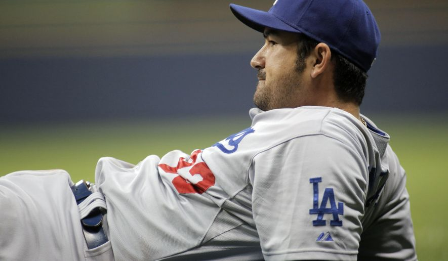 Los Angeles Dodgers first baseman Adrian Gonzalez takes a moment after diving for a missed foul ball against the Milwaukee Brewers during the seventh inning of a baseball game Friday, Aug. 8, 2014, in Milwaukee. (AP Photo/Darren Hauck)