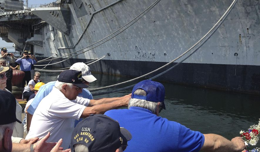 Veterans of the decommissioned aircraft carrier USS Saratoga place a wreath into the water beside the vessel during a farewell ceremony at Naval Station Newport Friday, Aug. 8, 2014 in Newport, R.I. The Saratoga will soon be towed to Texas to be dismantled. (AP Photo/Jennifer McDermott)