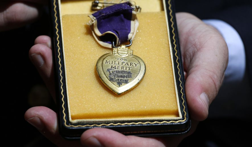 Purple Hearts Reunited founder Capt. Zachariah Fike, who was wounded in Afghanistan while serving with the Vermont Army National Guard, displays a Purple Heart from Pearl Harbor which has yet to be reunited with its owner or relatives, during the National Order of the Purple Heart National Convention in Denver, Thursday Aug. 7, 2014. (AP Photo/Brennan Linsley)