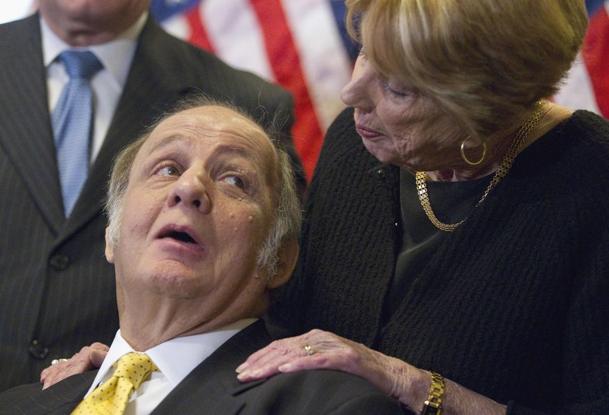 ** FILE ** This March 30, 2011, file photo shows former White House press secretary James Brady, left, who was left paralyzed in the Reagan assassination attempt, looking at his wife Sarah Brady, during a news conference on Capitol Hill in Washington marking the 30th anniversary of the shooting. This week's death of former White House press secretary James Brady, who survived a gunshot wound to the head in a 1981 assassination attempt on President Ronald Reagan, has been ruled a homicide, District of Columbia police said Friday, Aug. 8, 2014. (AP Photo/Evan Vucci, File)
