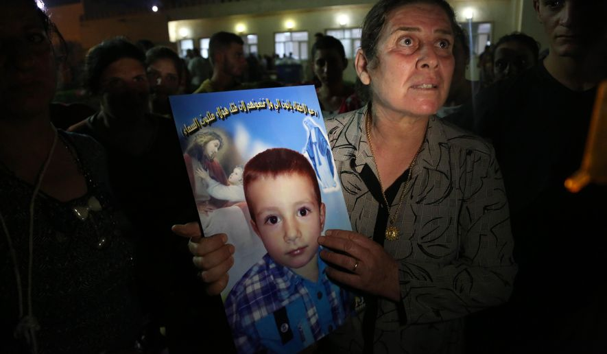 A displaced Iraqi Christian woman holds a picture of her four-year-old relative, David, who was killed by militants, at St. Joseph Church in Irbil, northern Iraq, Thursday, Aug. 7, 2014. Late Wednesday, militants overran a cluster of predominantly Christian villages alongside the country's semi-autonomous Kurdish region, sending tens of thousands of civilians and Kurdish fighters fleeing from the area, several priests in northern Iraq said Thursday. (AP Photo/Khalid Mohammed)
