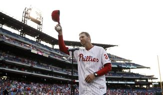 Former Philadelphia Phillies pitcher Roy Halladay tips his cap to the crowd after speaking before a baseball game against the New York Mets, Friday, Aug. 8, 2014, in Philadelphia. Halladay threw out the ceremonial first pitch in his first appearance at the stadium since retiring last season. (AP Photo/Matt Slocum) **FILE**
